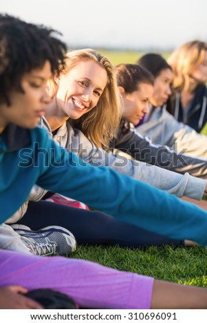 Portrait of smiling sporty blonde stretching during fitness class in parkland - stock photo