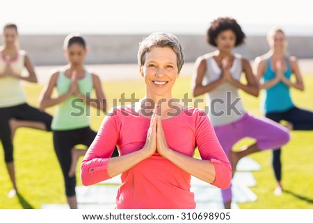 Portrait of smiling sporty woman doing yoga in yoga class in parkland - stock photo
