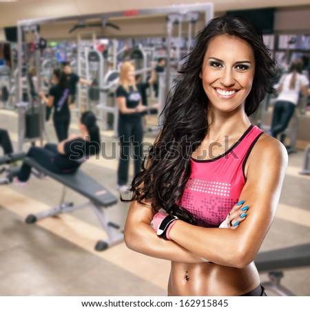 Portrait of smiling sporty woman in gym - stock photo