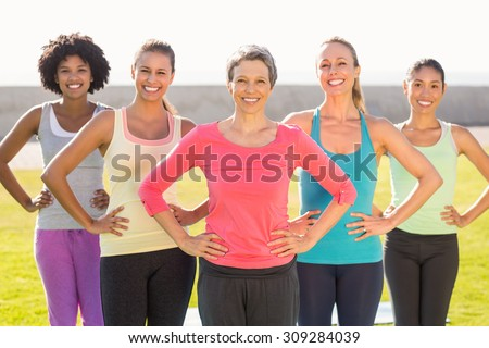 Portrait of smiling sporty women with hands on hips in parkland - stock photo