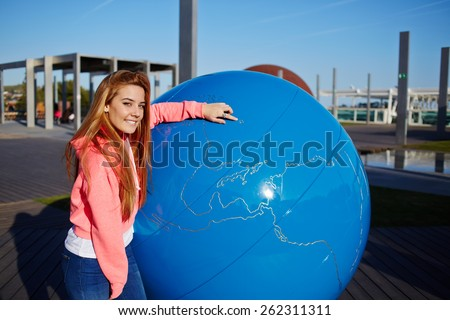 Portrait of smiling student girl pointing to the earth globe standing on school campus, science art globe object, attractive female teenager standing near big world globe outdoors - stock photo