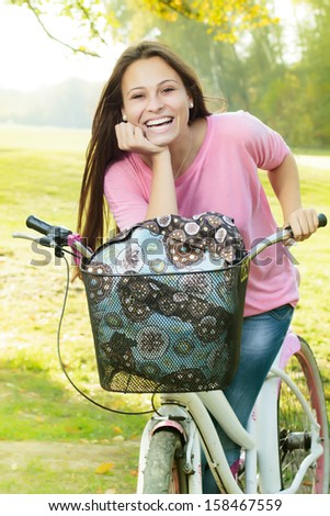 Portrait of smiling student girl with bicycle in the park. - stock photo