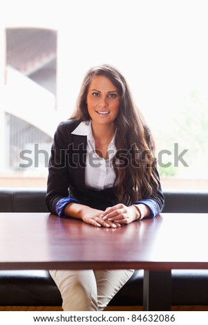 Portrait of smiling student sitting at a table - stock photo