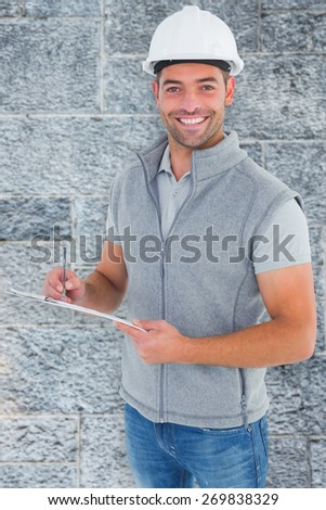 Portrait of smiling supervisor writing on clipboard against grey - stock photo