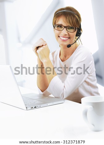 Portrait of smiling support phone operator in headset sitting at desk in front of laptop at her workplace. - stock photo