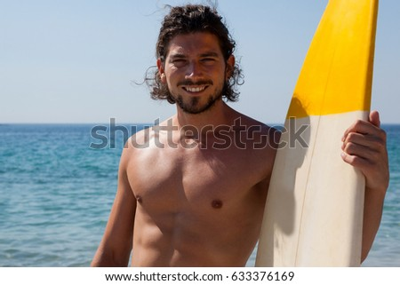 Portrait of smiling surfer with surfboard standing at beach coast