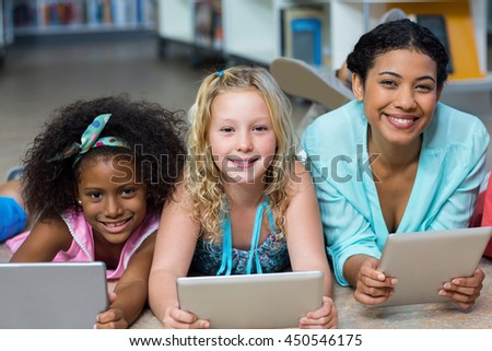Portrait of smiling teacher with girls using digital tablets while lying on floor in library