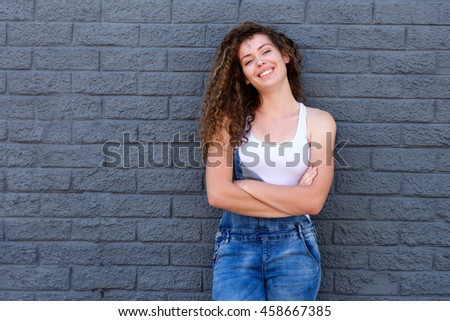 Portrait of smiling teen girl standing confidently against gray bricks - stock photo