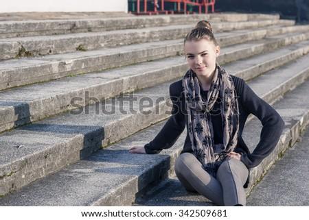 Portrait of Smiling Teenage Caucasian Girl on Stairs. Horizontal Image Orientation - stock photo