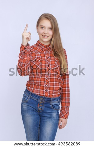 portrait of smiling teenage girl in shirt showing on something