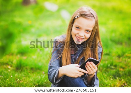 portrait of smiling teenage girl sitting in park and texting sms using mobile phone - stock photo