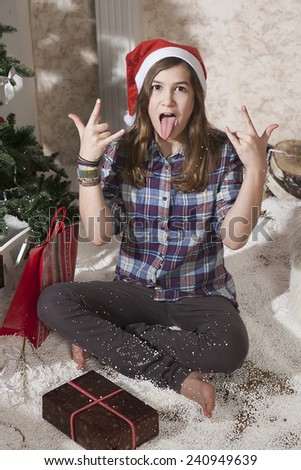 Portrait of smiling teenager girl in santa hat holding christmas present box and shout. She is sitting on artificial snow - stock photo