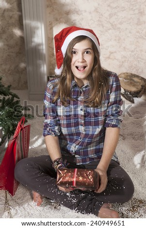 Portrait of smiling teenager girl in santa hat holding christmas present box and winking - stock photo