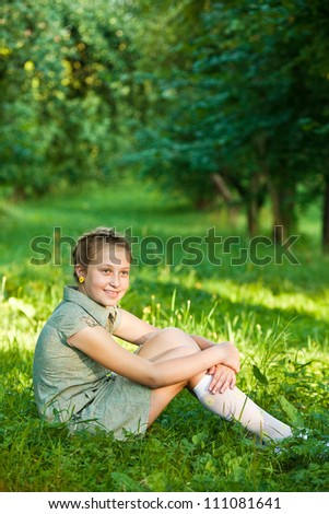 Portrait of smiling teenager girl sitting on grass in park