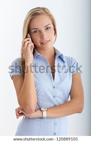 Portrait of smiling teenager on mobile phone call, looking at camera.