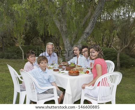 Portrait of smiling three generation family sitting at garden dining table - stock photo