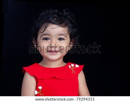 Portrait of Smiling Toddler Girl on Black Background - stock photo