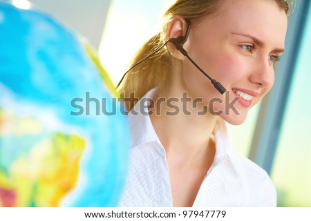 Portrait of smiling tour agent with headset consulting client online - stock photo