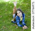 Portrait of Smiling Tween Girl lying On Grass Smiling To Camera - stock photo