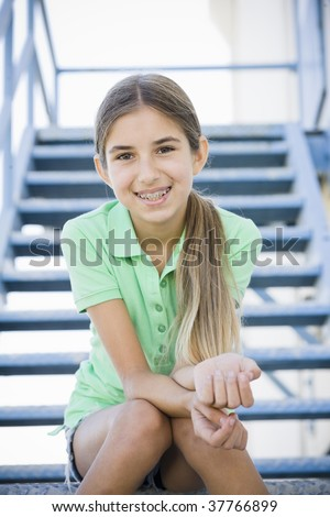 Portrait of Smiling Tween Girl Sitting On Stairway - stock photo