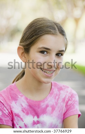 Portrait of Smiling Tween Girl with Braces  Wearing Tye-dyed T-Shirt - stock photo