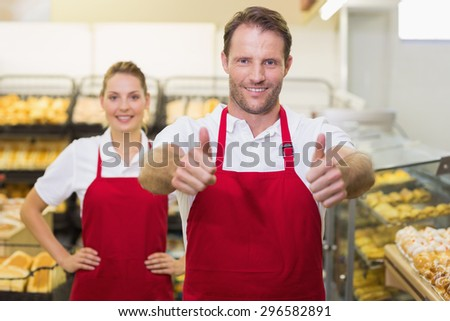 Portrait of smiling two bakers with thumb up in bakery - stock photo