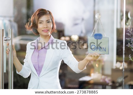 POrtrait of smiling Vietnamese business woman opening store