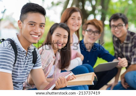 Portrait of smiling Vietnamese student on the background of his cheerful classmates - stock photo