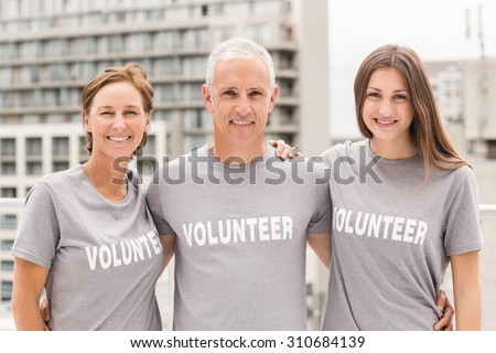 Portrait of smiling volunteers putting arms around each other on roof of building - stock photo