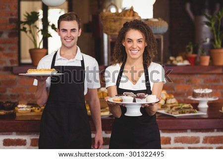 Portrait of smiling waiter and waitress showing plates with treat at coffee shop - stock photo