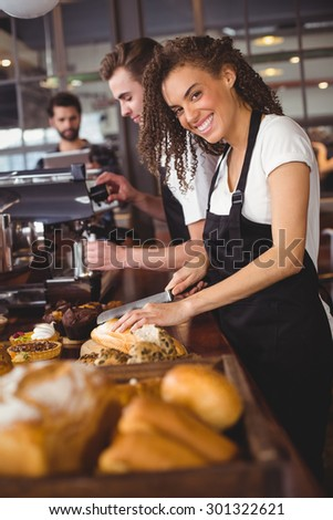 Portrait of smiling waitress cutting bread in front of colleague at coffee shop - stock photo