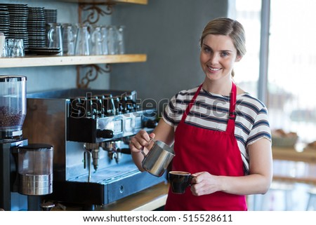Portrait of smiling waitress making cup of coffee at counter in cafe