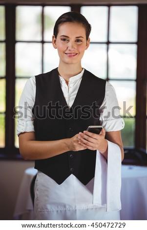 Portrait of smiling waitress standing in restaurant using mobile phone - stock photo