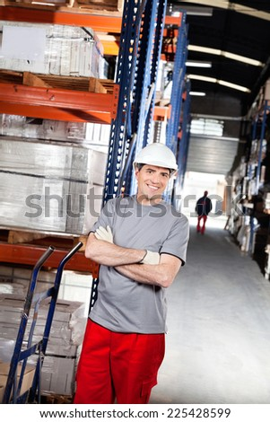 Portrait of smiling warehouse worker with handtruck at warehouse - stock photo