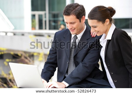 Portrait of smiling woman and man with a laptop computer - stock photo