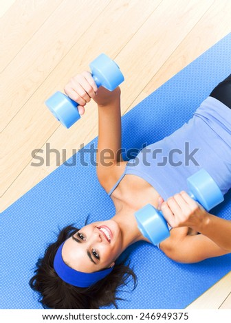 Portrait of smiling woman exercising with dumbbells, indoors or in fitness center