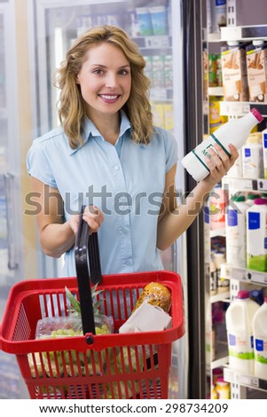 Portrait of smiling woman having on her hands a fresh milk bottle and shopping basket in supermarket - stock photo