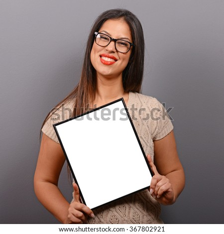 Portrait of smiling woman holding blank photo frame against gray background