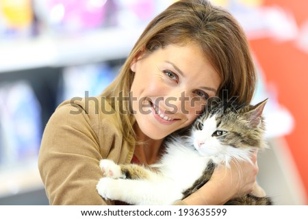 Portrait of smiling woman holding cat  - stock photo