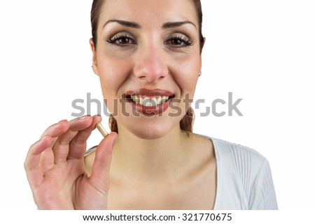 Portrait of smiling woman holding pill against white background - stock photo