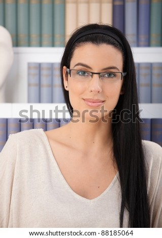 Portrait of smiling woman in glasses looking at camera in front of book shelf.? - stock photo