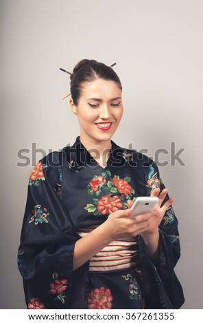 Portrait of smiling woman in kimono holding mobile phone  - stock photo