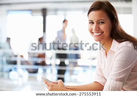 Portrait of smiling woman in office with telephone - stock photo