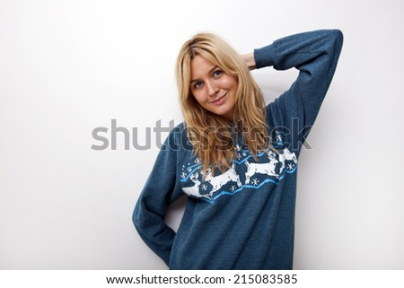 Portrait of smiling woman in sweater against white background - stock photo