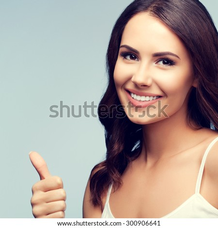 Portrait of smiling woman in white tank top clothing, showing thumb up gesture - stock photo