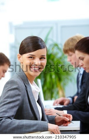 Portrait of smiling woman looking at camera on the background of working colleagues - stock photo