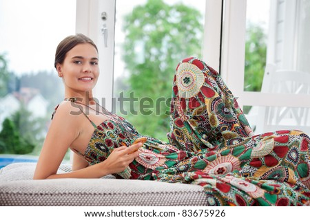 Portrait of smiling woman on bed holding cell phone - stock photo