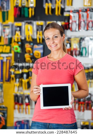Portrait of smiling woman presenting digital tablet in hardware shop