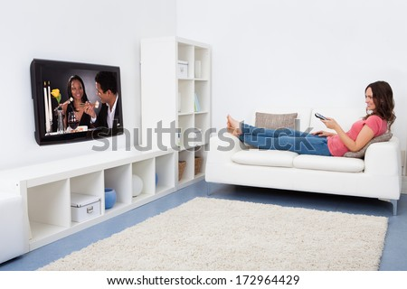 Portrait Of Smiling Woman Sitting On Couch Watching Television - stock photo