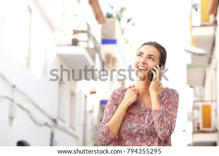 Portrait of smiling woman talking on mobile phone outside on street